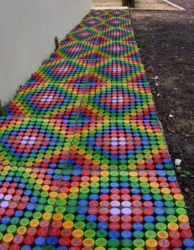 Sidewalk lined with bottle caps